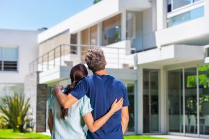 couple embracing in front of new big modern house, outdoor rear view back looking at their dream home