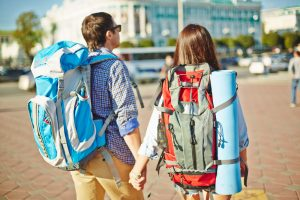 Affectionate travelers with rucksacks walking down unknown city